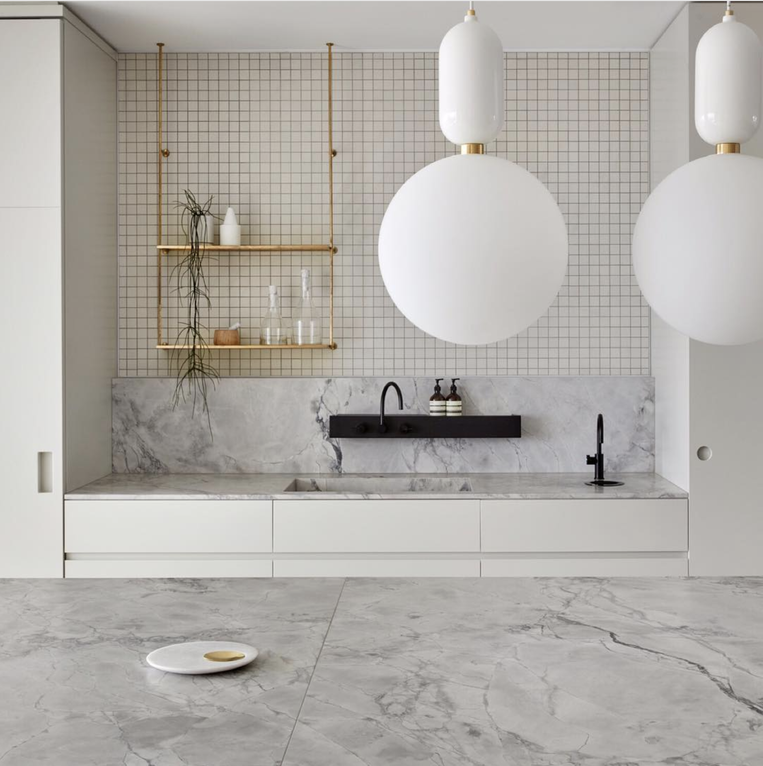 Source . In addition to having these spectacular lights that echo the moon shape, this kitchen is one of the more amazing spaces that I've seen recently.