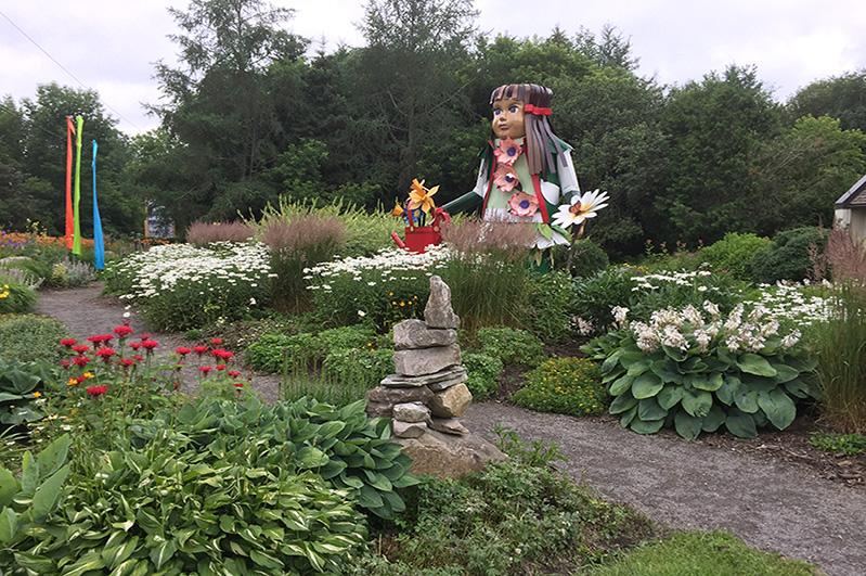 Jardin d'accueil avec notre mascotte Angelica et notre 'inukshuk' maison