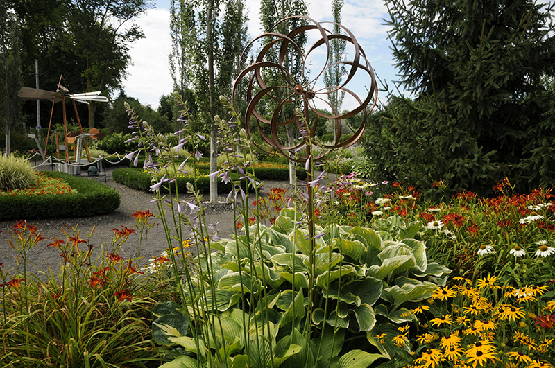 Jardin des Découvertes (contemporain moderne) avec vire-vent, sculpture, Hosta, rudbeckies, hémérocalles