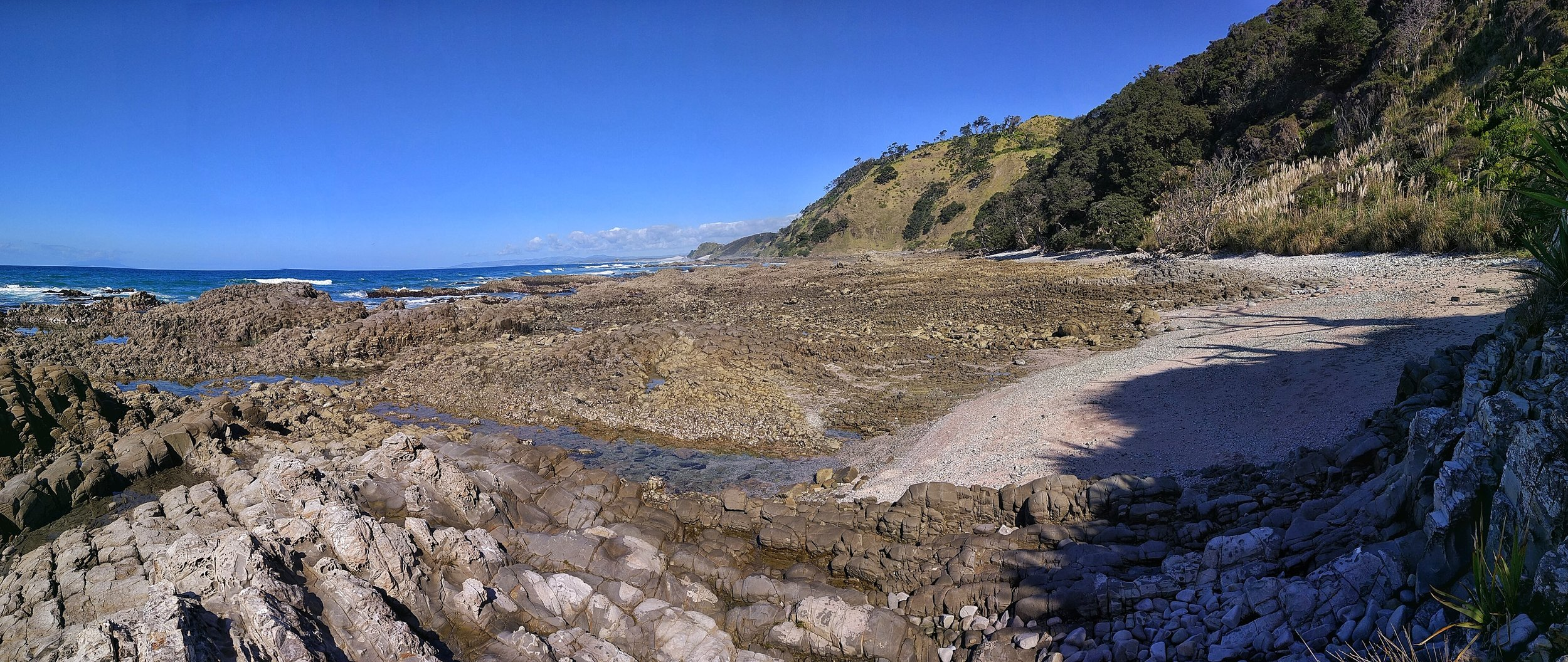 Walking on rocky terrain on the water level part of Mangawhai Walkway