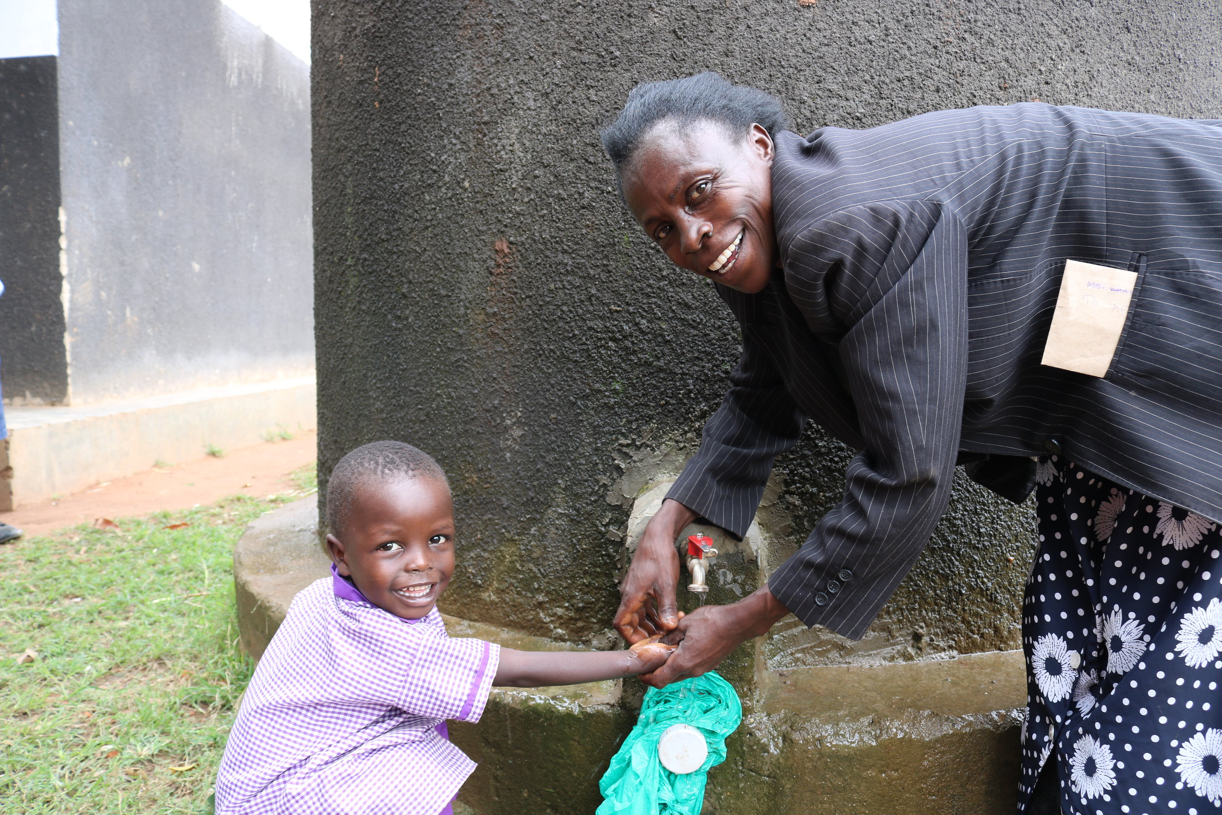 At a local school, this teacher is very proud of their rainwater harvesting set up! With the Blue Tap technology these school children will be able to drink the water too!