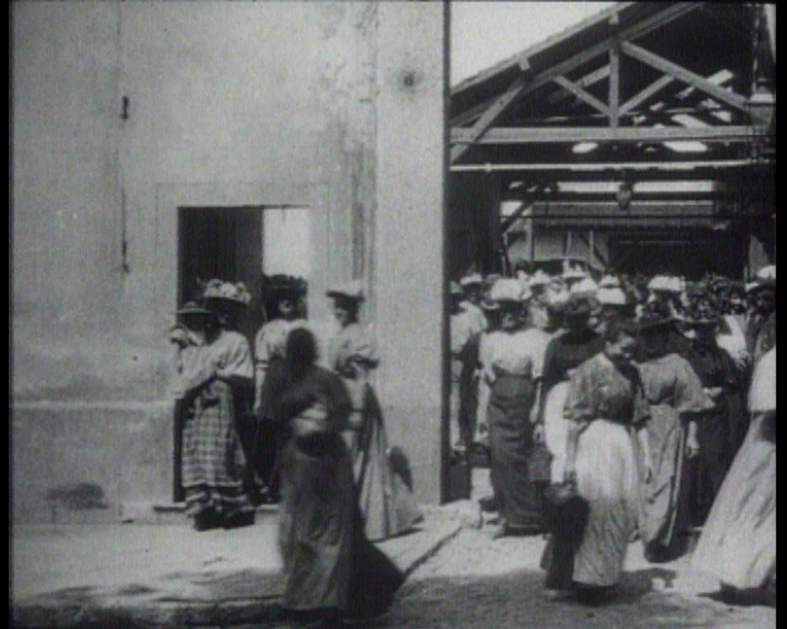 《工人离开工厂》,1995年,艺术家提供图片 Workers leaving the Factory, 1995, ©Harun Farocki 《工人离开工厂》是电影史上第一部公开放映的电影的名字。时长45秒,这部片子展现了里昂卢米埃兄弟的摄影产品工厂里的工人,摩肩接踵,匆匆从工厂大门的阴影中走出来,进入到下午的阳光里。只有在这里,工人们匆匆离去,他们才可视为一个社会群体。但是,他们要去往何处?去参加一个集会?还是遇见一个街垒?或是回家?这些问题被一代又一代的纪录片制作人所关注。工厂大门前的空间则一直被当做社会冲突的场景。而且,这部片子已成为电影史上叙事媒介的一个代表作品。在法罗基关于纪录片所作的同名文章中,他通过电影史探讨了这个场景。这一努力的结果就是成就了一篇从摄影媒介本身出发的出色电影分析,范围涉及广泛,从卓别林的《摩登时代》到弗里茨·朗的《大都会》,再到帕索里尼的《寄生虫》。如法罗基的电影所示,卢米埃兄弟的片子在其内部就蕴含着可预见的社会发展之萌芽:这种形式的工业劳动会终将消失殆尽。(克劳斯·格林豪恩,Hildesheimer Allgemeine Zeitung,1995年11月21日)。 Workers Leaving the Factory - such was the title of the first cinema film ever shown in public. For 45 seconds, this stillexistant sequence depicts workers at the photographic products factory in Lyon owned by the brothers Louis and Auguste Lumière hurrying, closely packed, out of the shadows of the factory gates and into the afternoon sun. Only here, in departing, are the workers visible as a social group. But where are they going? To a meeting? To the barricades? Or simply home? These questions have preoccupied generations of documentary filmmakers. For the space before the factory gates has always been the scene of social conflicts. And furthermore, this sequence has become an icon of the narrative medium in the history of the cinema. In his documentary essay of the same title, Harun Farocki explores this scene right through the history of film. The result of this effort is a fascinating cinematographic analysis in the medium of cinematography itself, ranging in scope from Chaplin's Modern Times to Fritz Lang's Metropolis to Pier Paolo Pasolini's Accattone!. Farocki's film shows that the Lumière brothers' sequence already carries within itself the germ of a foreseeable social development: the eventual disappearance of this form of industrial labor. (Klaus Gronenborn, Hildesheimer Allgemeine Zeitung, November 21, 1995)