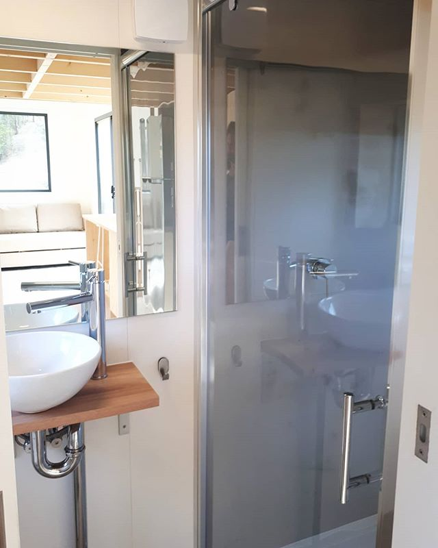Sowelo 7m Zen fully offgrid. Bathroom with rain shower, hand made ceramic basin, quality taps and fixtures, large mirror and custom storage. All glues and coatings no or Low VOC. www.sowelotinyhouses.com.au #Tinyhousesaustralia #tinyhouseonwheels #sustainable #environmental #offgridsolar #offgridliving #ecofriendly #ecobuilding #sowelotinyhouses #lowvocs #livingbiginatinyhouse #minimalism