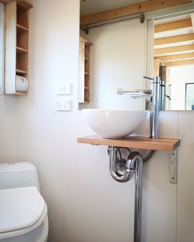 Sowelo 7m Zen fully off grid. Bathroom with composting toilet, hand made ceramic sink, large mirror and custom storage, rain shower and instant gas hot water system. www.sowelotinyhouses.com.au #lowvocs #environmental #sustainable #Tinyhousesaustralia #tinyhouseonwheels #ecofriendly #minimalism #offgrid #offgridsolar #sowelotinyhouses #livingoffgrid #livingbiginatinyhouse