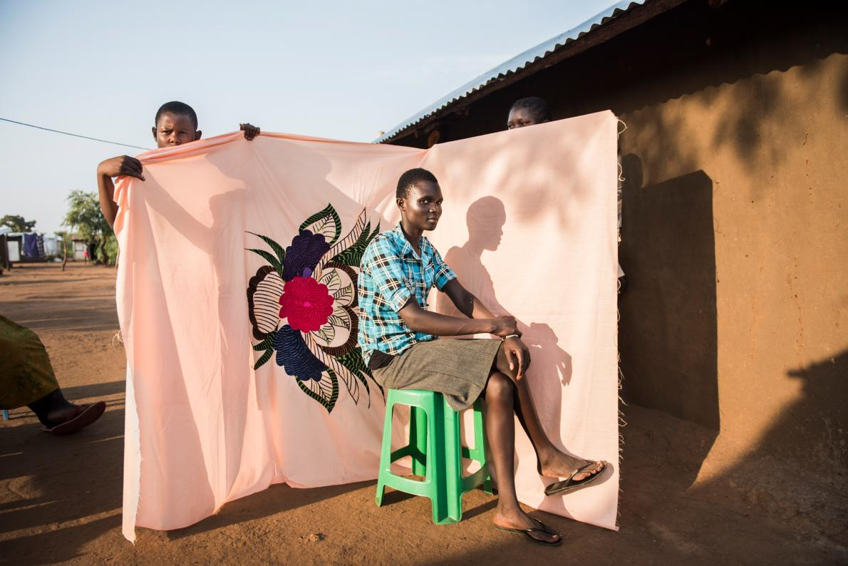 Irene Sonia poses in front of a milaya, or bedsheet—one of the few things her mother managed to bring when they fled South Sudan for Uganda. by NORA LOREK
