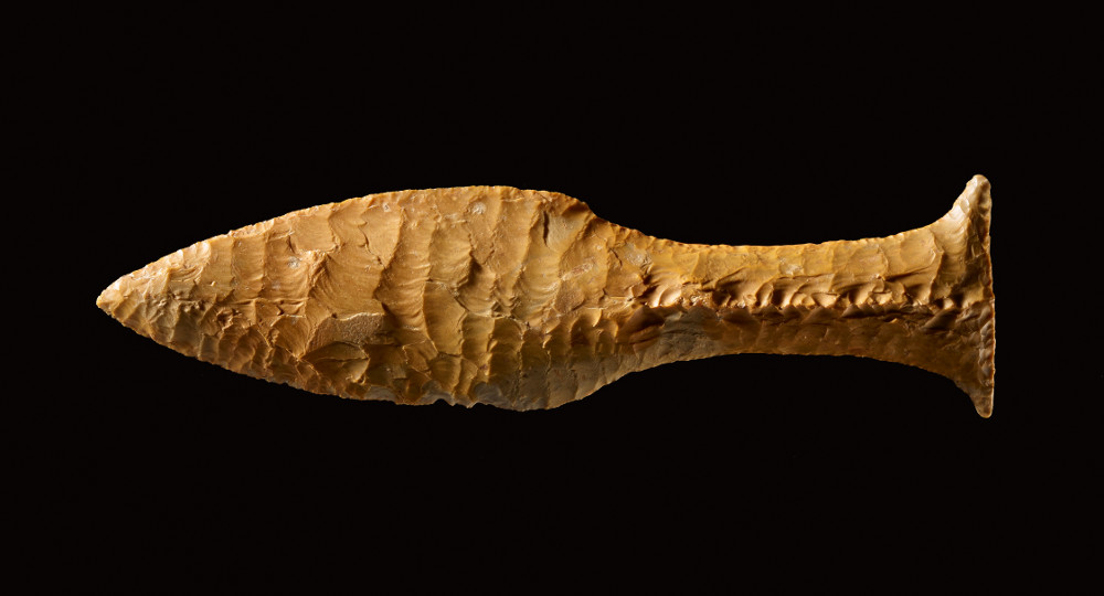 Fish-tail dagger - Flint2400–2000 BCDenmarkBritish MuseumThe Neolithic and Bronze Age periods in Europe saw the development of specialised tools, including daggers, which were knives or weapons with a pointed blade made out of stone. This example is made of dark yellow flint, a stone favoured because it splits relatively easily into thin, sharp splinters. With a triangular fish-tail handle and a peculiar seam detail, the flint has been worked with remarkable craftsmanship in order to make this tool to look like a bronze dagger.