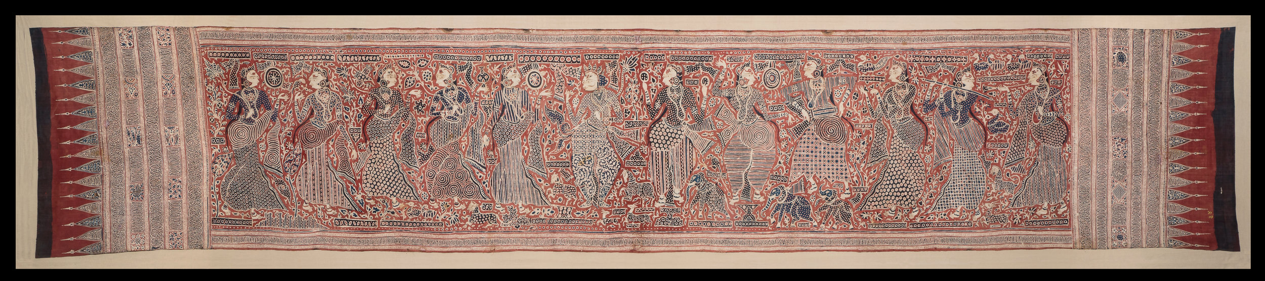 Heirloom textile - Cotton, mordant and resist-dyedAbout AD 1500Made in Gujarat, India; found in Sulawesi, IndonesiaTAPI Collection of Praful and Shilpa Shah, SuratMost Gujarati textiles for the Indonesian market were block-printed, however, some were highly valued heirlooms. This hand-painted textile shows a shahi king with five nayikas or surasundaris (celestial beauties). Behind him are six female musicians and dancers. The costumes are also varied – the ladies wear a ghagra skirt and dhoti, while the king is in tailored salwar-style trousers. Interestingly, he is wearing boots that are Central Asian in origin.