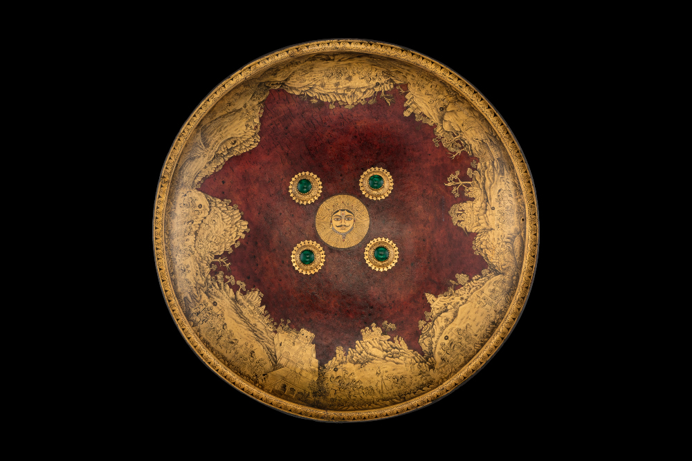 Shield of Maharana Sangram Singh II  - Shield (dhal) of Maharana Sangram Singh IIMewar, About AD 1730Udaipur, Rajasthan, India National Museum, New DelhiThe subject of the painting on this shield is Maharana Sangram Singh II – ruler of the Rajput court of Mewar from 1690 to 1734. He is shown practicing his archery, hunting tigers, and having amorous encounters in the forest, while the women of the court expectantly await his return. Messengers would carry a royal shield to allow them a safe and speedy passage, and in Rajput courts they had long been used as trays for royal gifts. The elegant dagger is of a type that was comfortably worn tucked in the sash-belt and could have been used by either a man or woman.