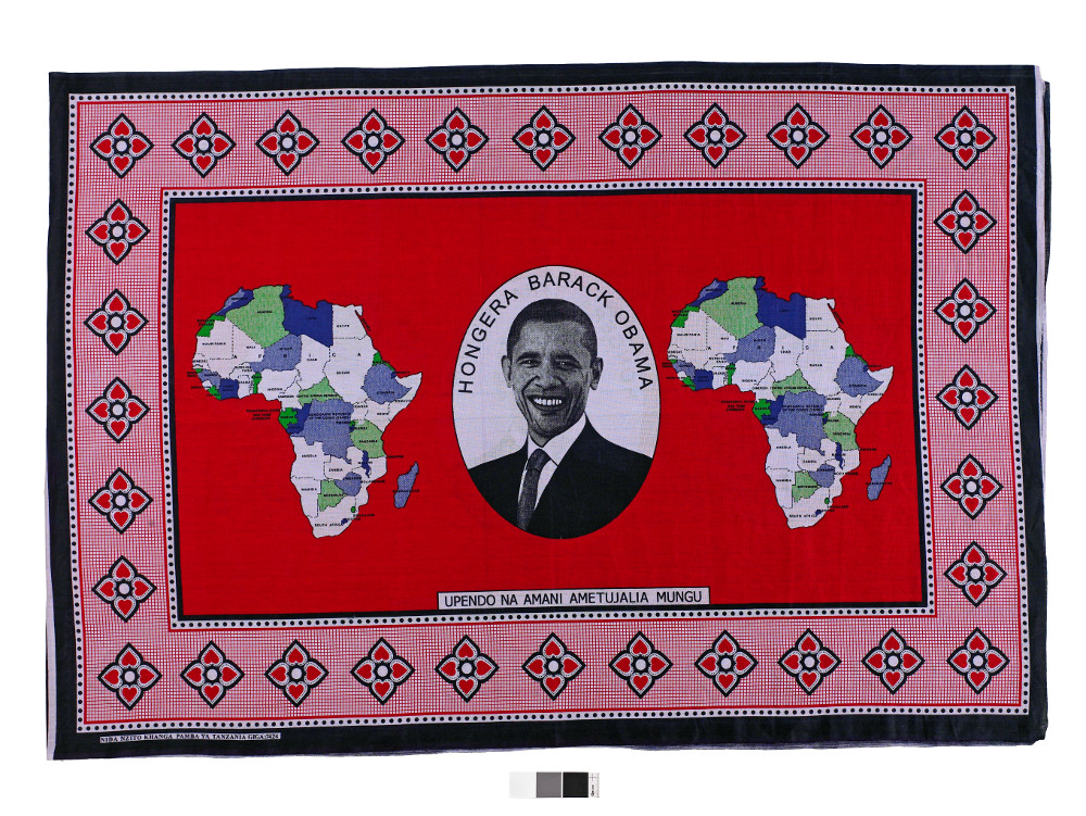 Barack Obama kanga  - Printed cottonAD 2008Made in Dar es Salaam, Tanzania; found in Nairobi, KenyaBritish MuseumThe design of kangas (East African garments), often reflects political and social change. This kanga celebrates Obama's first election to the United States Presidency in 2008, and reads: 'Congratulations Barack Obama', and, 'god has blessed us with love and peace'. Of partial Kenyan descent, Barack Obama was the first African American to hold the US Presidency. This kanga was printed in Tanzania but was worn throughout East Africa, particularly in Kenya, where his election was widely celebrated.