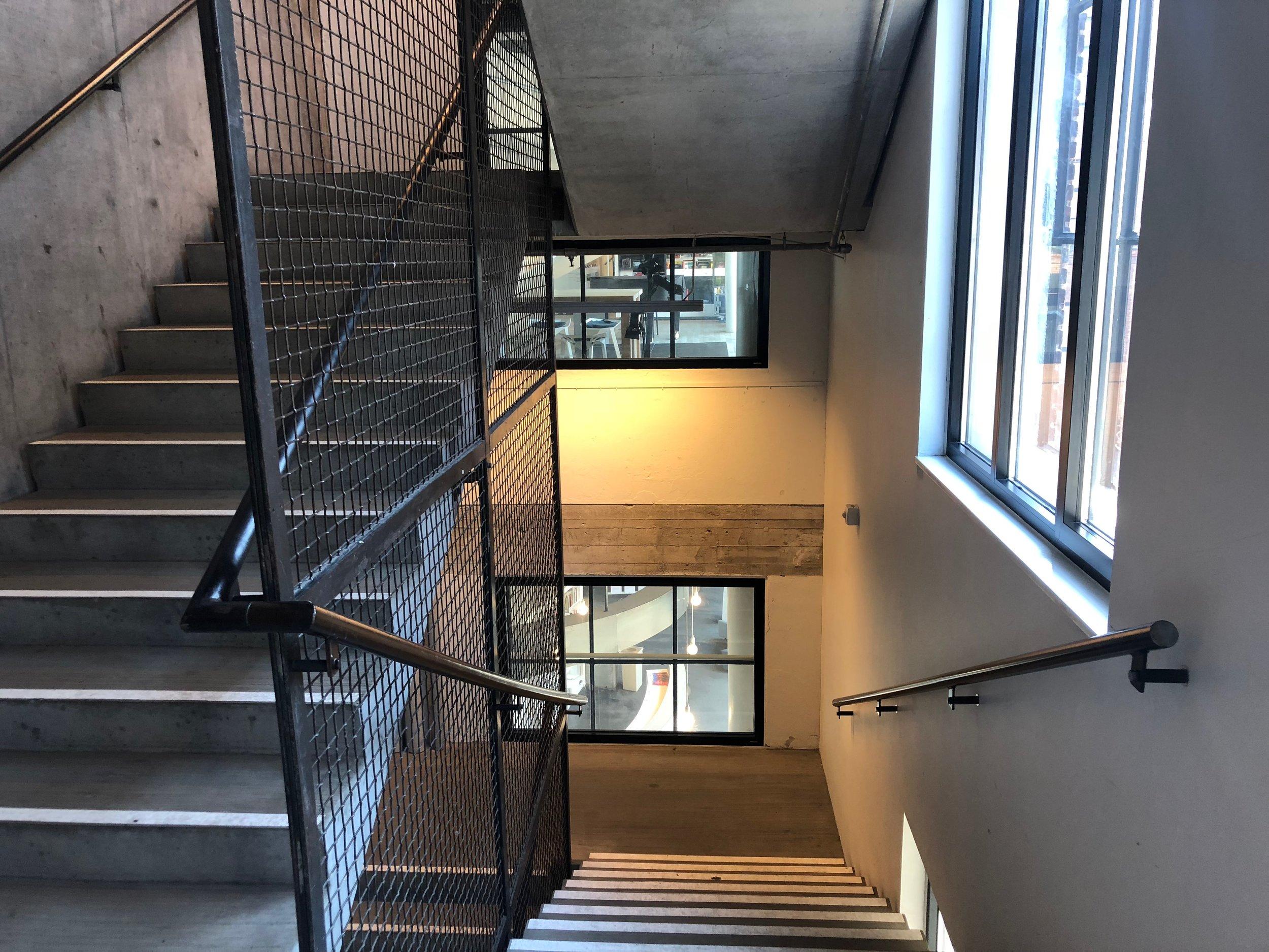 En ny beton trappe er sat ind i den gamle bygning. Den passer godt ind, da den har et meget råt udtryk