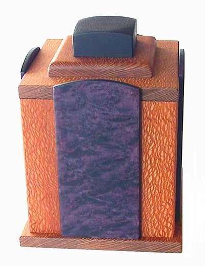Cuenca    – 2013 – Funerary Urn – Reflecting the Spanish town of Cuenca with its dramatic almost sheer rock walls and vivid and rich colours and history.    20cm W x 20cm L x 28cm H – inner top has a birds eye Maple panel with a crucifix cut into it, lined with purple Silk.    Dyed Birdseye Maple / Lacewood / Ebonized Maple / SilkBeeswax. SOLD