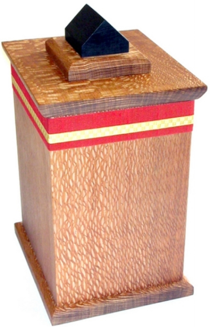 Dignitas    – 2010 – Funerary Urn with red Silk lined interior compartment.    15cm W x 18.75cm L x 31.75cm H    Lacewood / Ebonized Maple / Silk / Metallic Ribbon.     PRIVATE COMMISSION