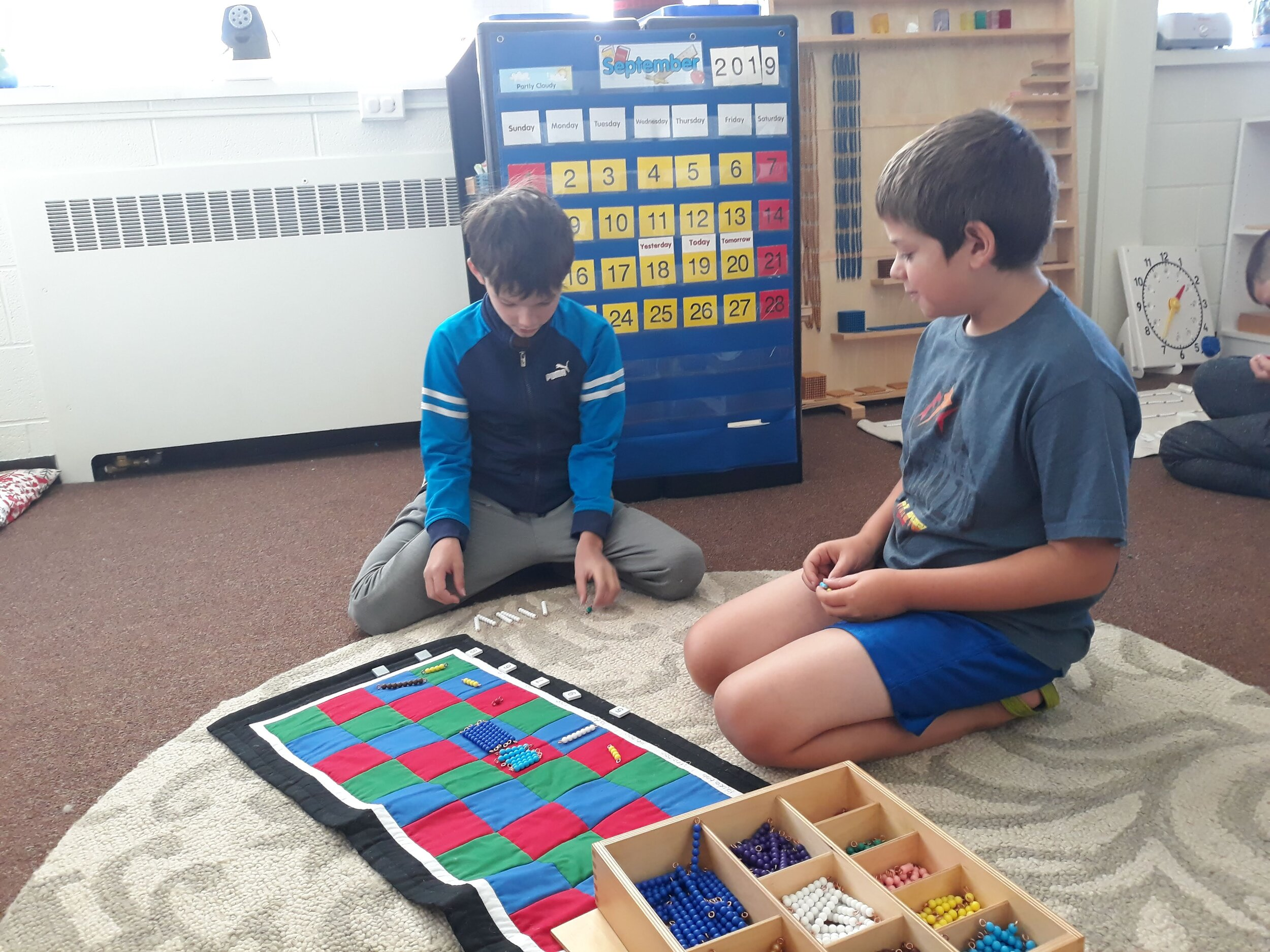 Students explaining math concepts to one another using Montessori materials