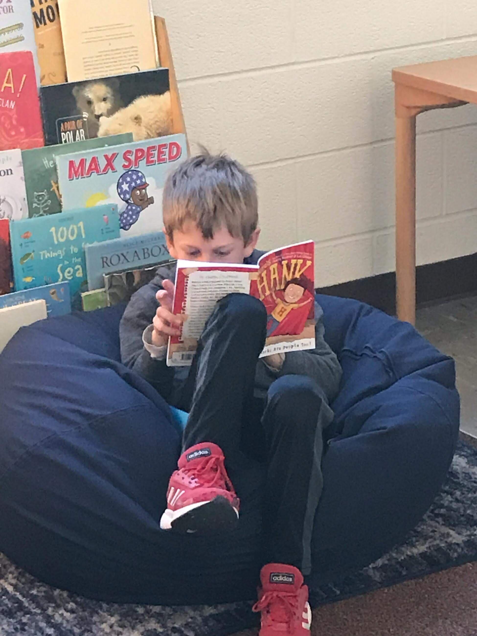 A student enjoying reading a Hank book