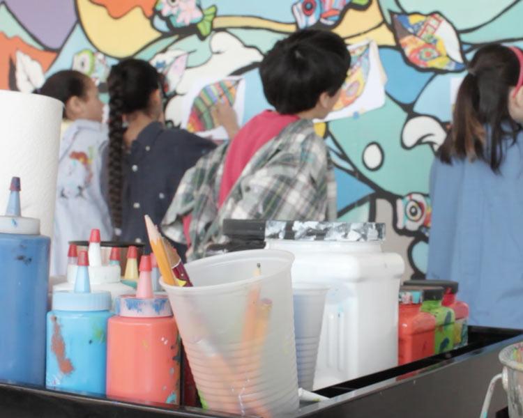 Children add their creative contributions to murals designed by Bayne Gardner.