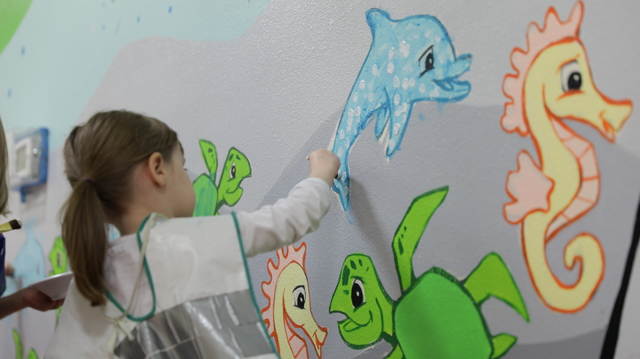 A child adds their own touch to the Pearl Buck mural.