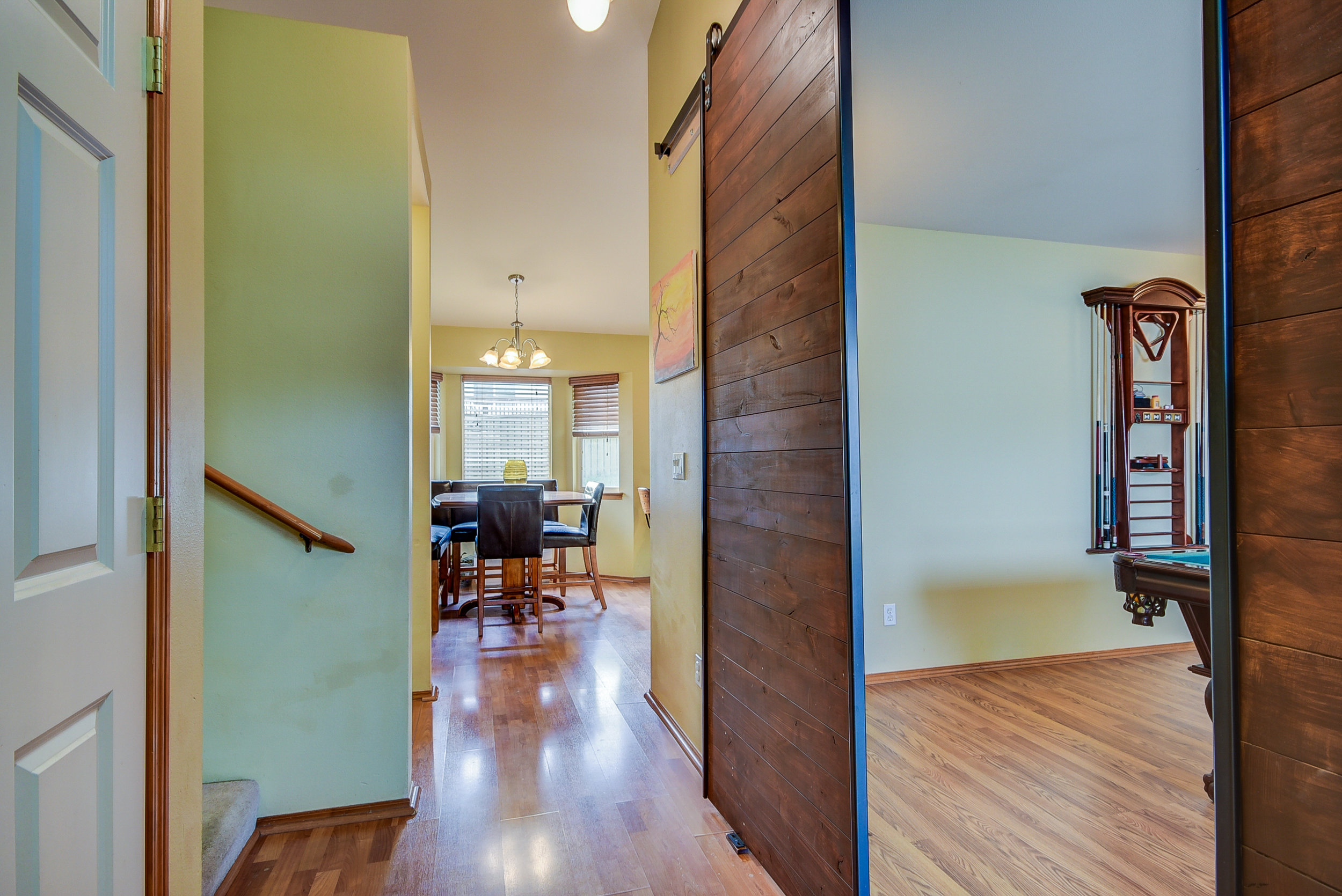 Newer laminate flooring on the main level..check out the amazing custom sliding doors that go into your oversized living room (currently the billiards room)!