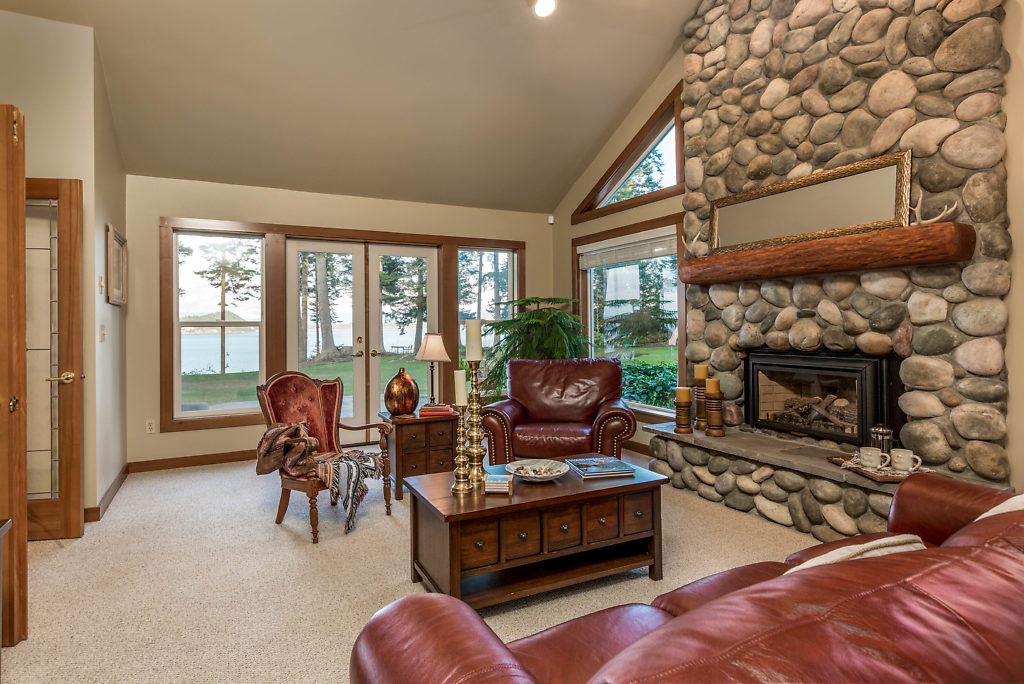 Beautiful living room with vaulted ceilings, river rock fireplace, and French doors that lead to your sunlit patio...