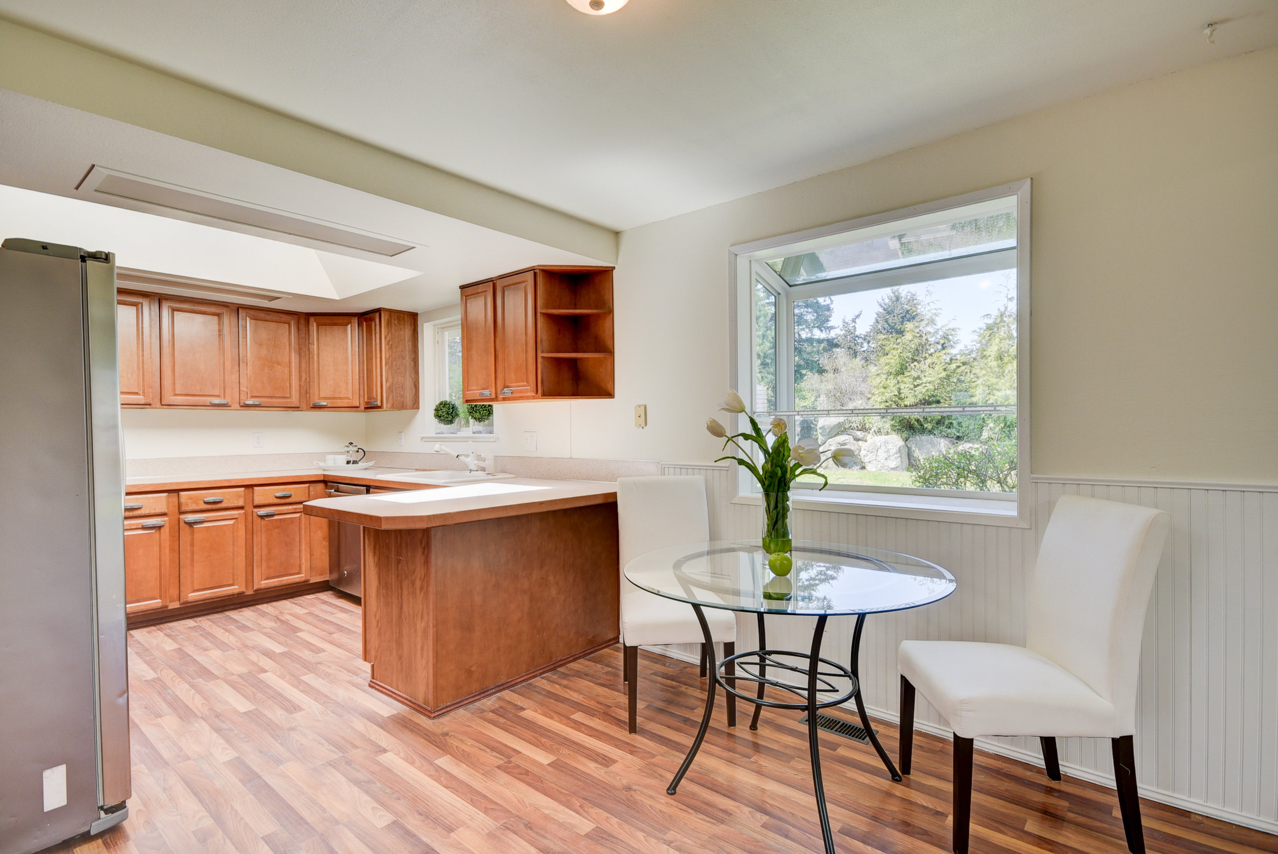 Maple cabinetry...stainless steel appliances, & another skylight & garden window let in tons of natural light...