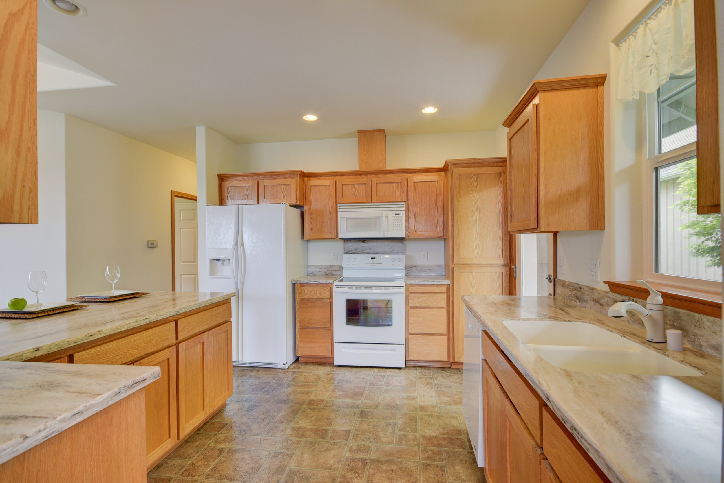 Generous kitchen with ample storage, upgraded counter-tops, & access to your private porch!