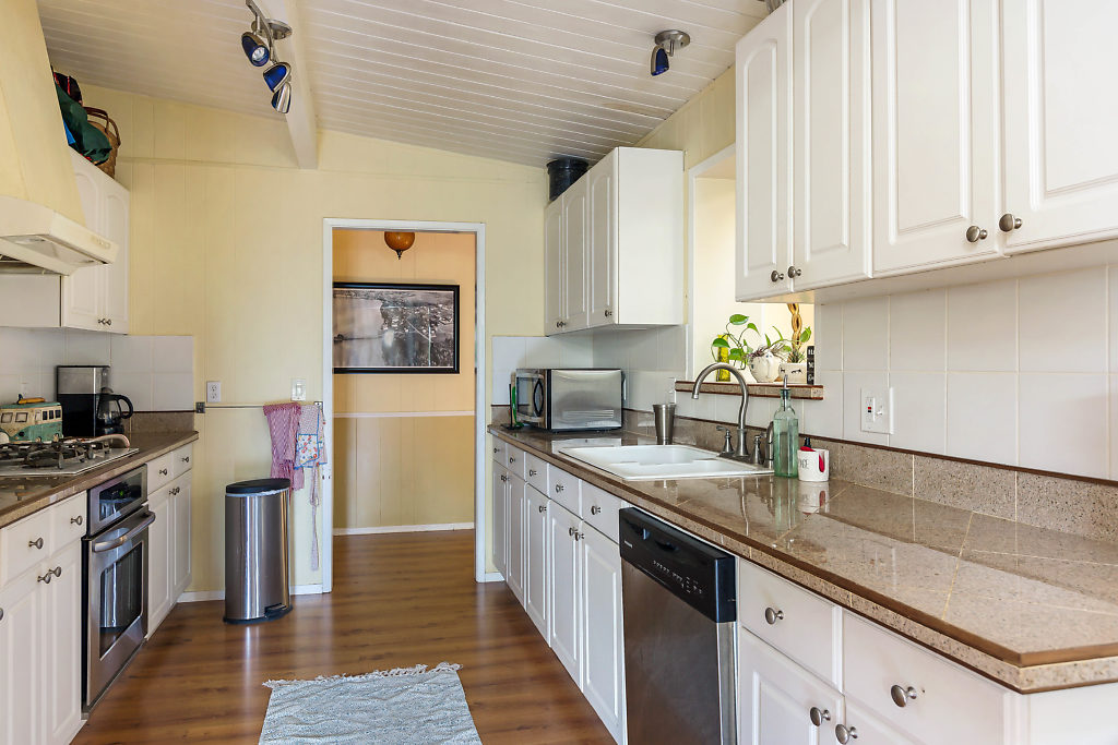 The kitchen with durable laminate floors, bright white cabinetry with custom pull-out shelves, granite counters, & quality appliances...