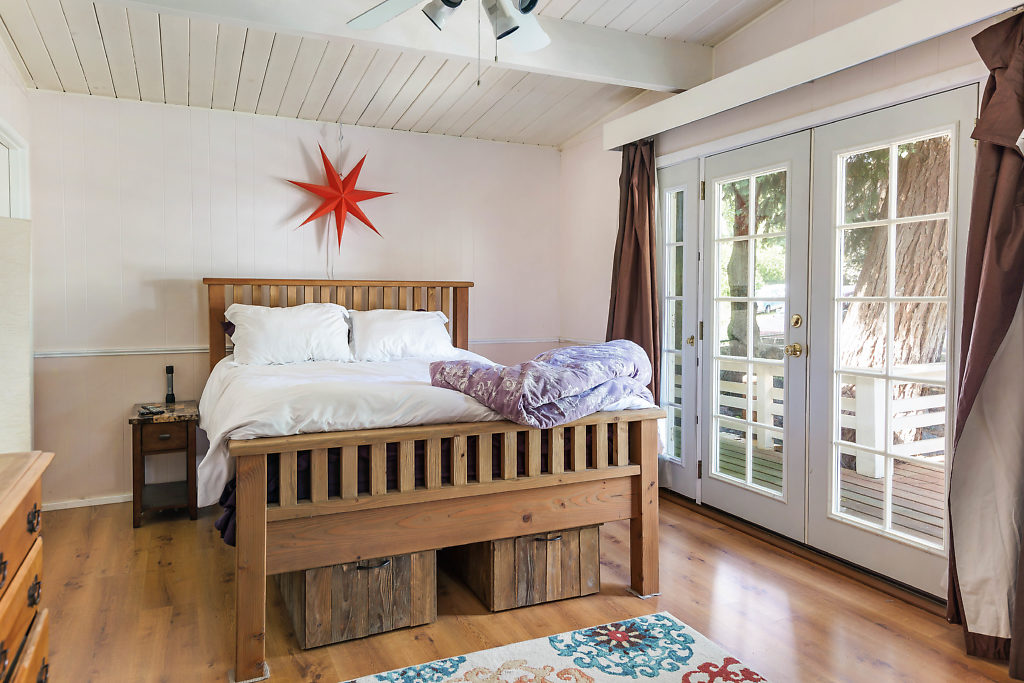 A beautiful master suite with French doors, laminate floors, huge walk in closet, and wood-wrapped ceiling...