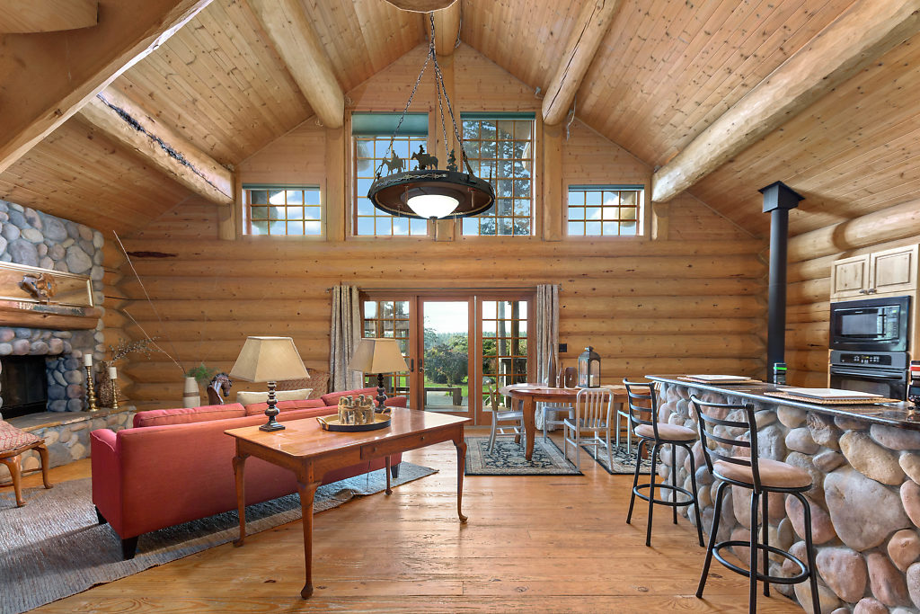 Wood-wrapped windows...exposed beams...French doors...2 fireplaces...this space glows with warmth & charm.