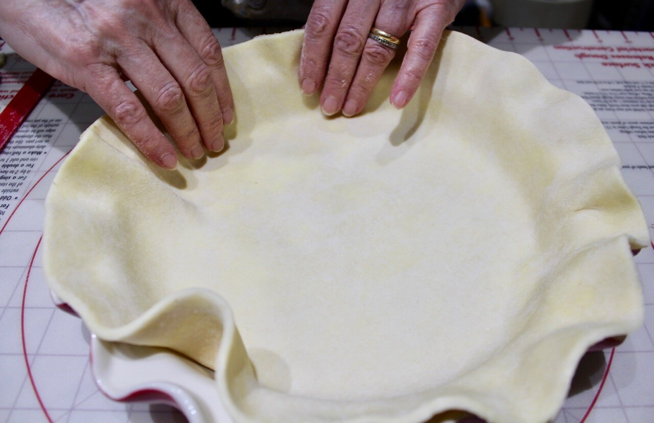 fitting bottom crust into the plate's scalloped border