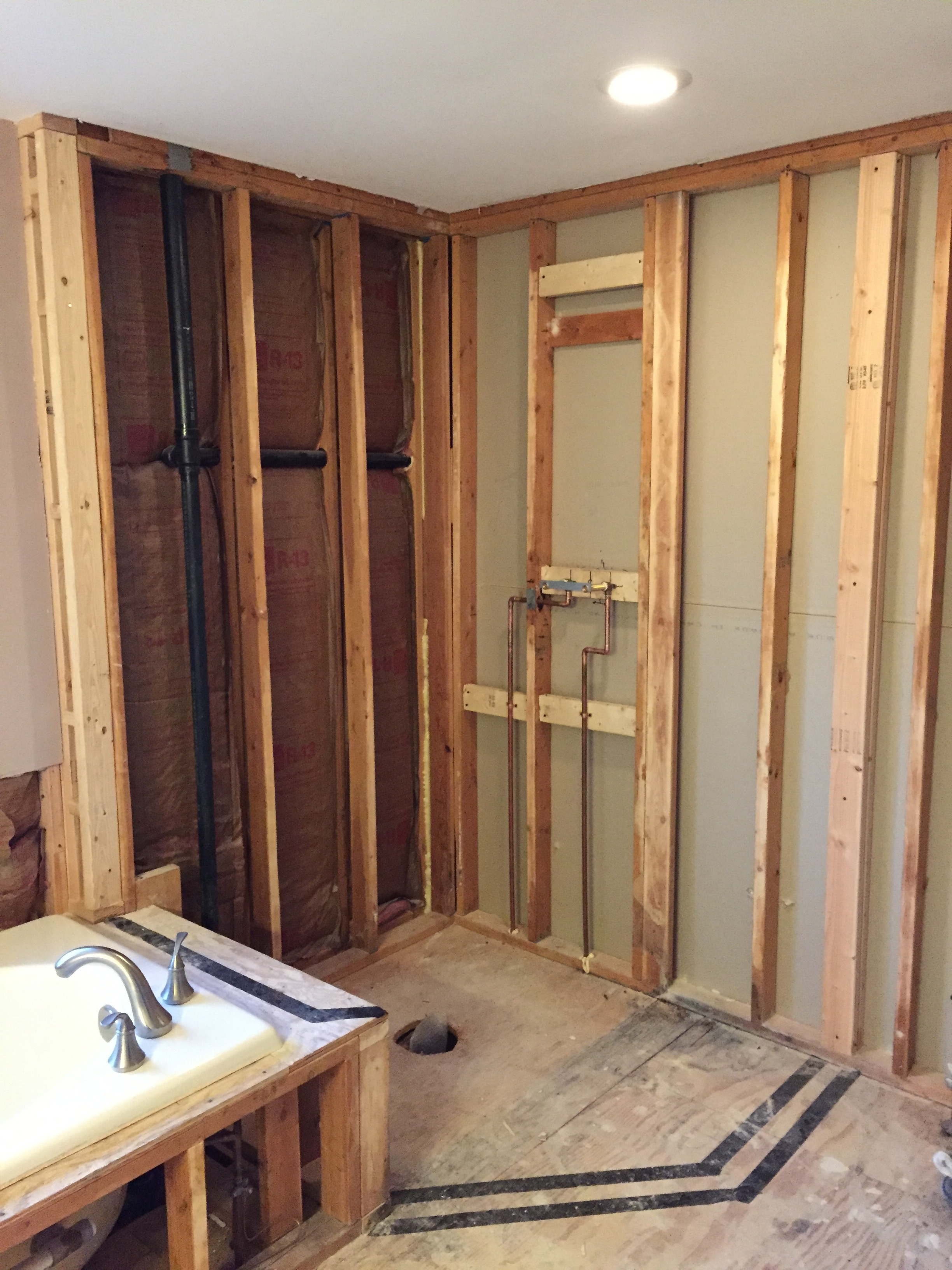"Shower Design - We used tape to map out the area for the shower trying to optimize the size while keeping in mind the width and clearance for the door and the building code for proximity to the toilet. The homeowners wanted a slightly thicker 1/2"" clear tempered glass rather than the typical 3/8"" thickness for a more dramatic frameless shower effect.  The trade-off was cost and needing to install a header to support the thicker, heavier glass and the 31"" door width.  An 80"" shower height was selected to make the nickel header less noticeable.  The design included a 5"" overhang on the tub platform to allow someone to comfortably rest a leg for shaving or washing.  Wall studs were added at each end of the shower in order to secure the heavy glass panels."