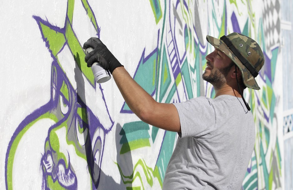 Graffitti artist Anthony Arias works on a mural during the Art Basel Miami Beach fair in 2014. Andrew Innerarity/Reuters