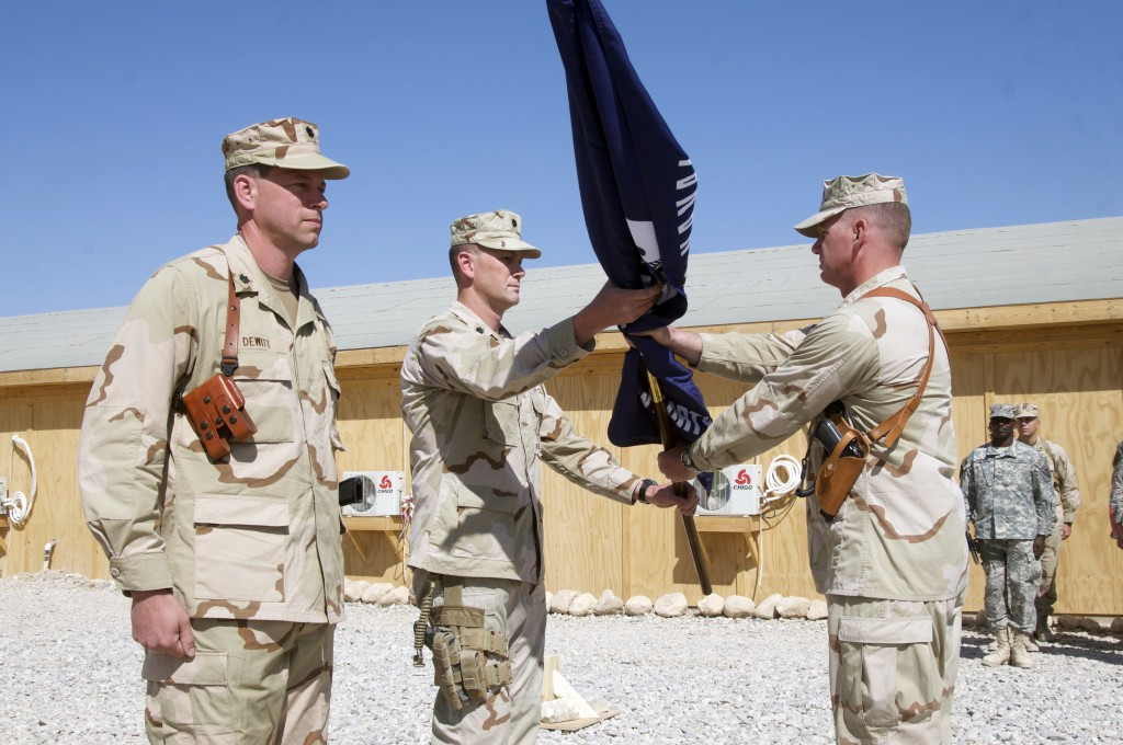 Naval Mobile Construction Battalion 40 conducts a change of command ceremony in Deh Dadi II, Afghanistan Sept. 24, 2010. Cmdr. Tim DeWitt (left) assumed command from Cmdr. Glenn Hubbard (center) who hands the battalion flag to Command Master Chief Corey Heinrich during the ceremony. (Photo by MCC Michael Watkins)