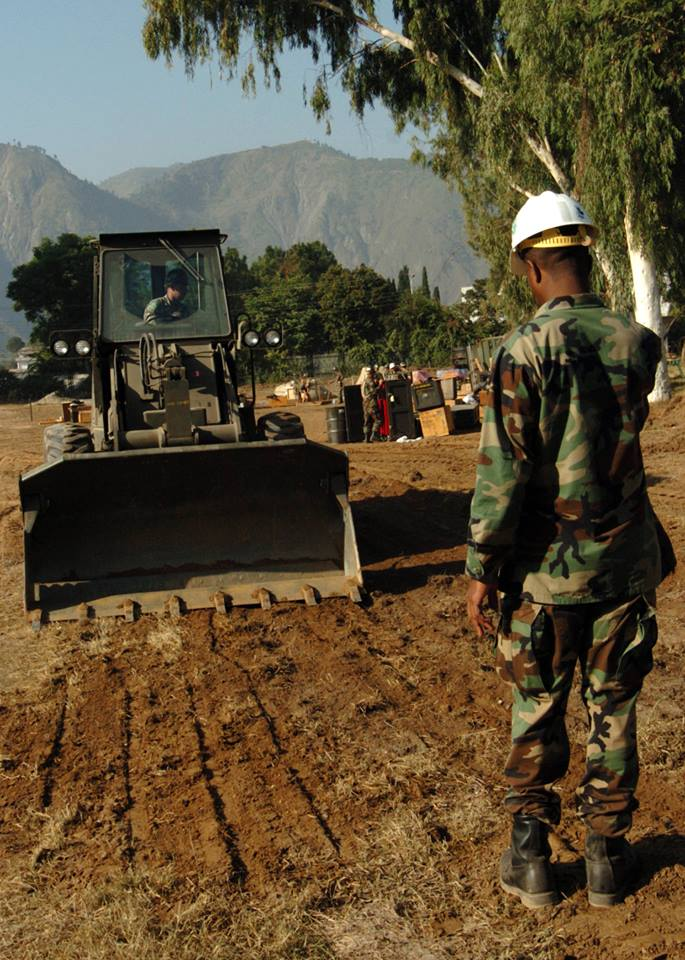 2005:    U.S. Navy Seabees assigned to the air detachment of Naval Mobile Construction Battalion Seven Four (NMCB-74), cleared the ground of foreign objects to set up their command operations center located in Muzafarrabad, Pakistan. The United States was participating in a multi-national assistance and support effort led by the Pakistani Government to bring aid to the victims of the devastating earthquake that struck the region on October 8, 2005. (Photo courtesy of U.S. Navy Seabee Museum)