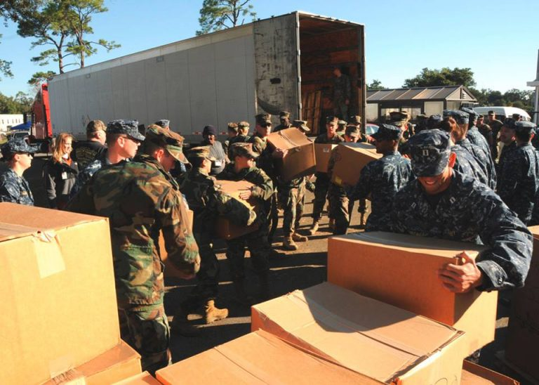 2010:   Seabees assigned to Naval Mobile Construction Battalion (NMCB) 133 and sailors from the guided-missile destroyer USS William P. Lawrence (DDG 110) unloaded supplies to be given to veterans during the VA Stand-Down in Biloxi, Miss. The VA Stand-Down is a one-day event providing free food, clothing, health screenings, Social Security benefits counseling and other services to homeless veterans in the Gulf Coast area. (Courtesy of U.S. Navy Seabee Museum)