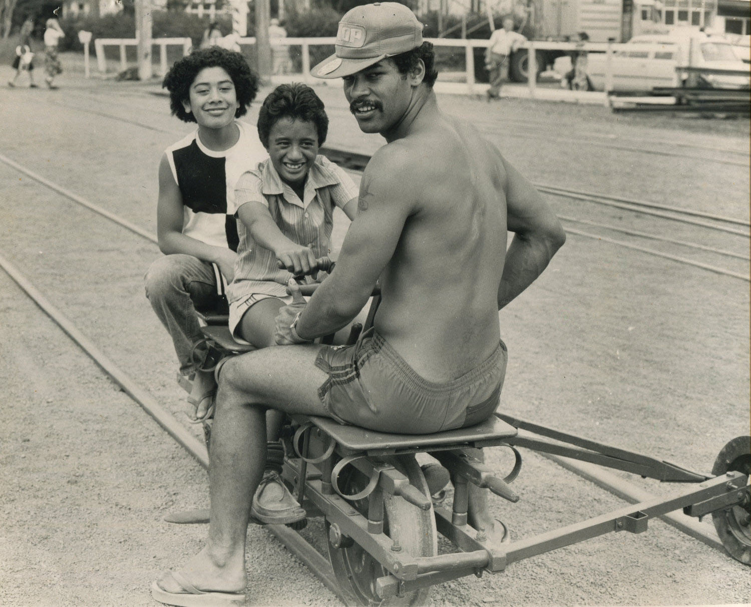 Mr James Lose, Kelston, gives two young visitors from Otara, Donni Takiari and Desmond Edwards, a jogger ride in the Henderson railroads during centennial celebrations, Henderson Rail Centenary, 21/03/1981. Photograph by the Western Leader. Auckland Libraries, Courtesy of West Auckland Research Centre.