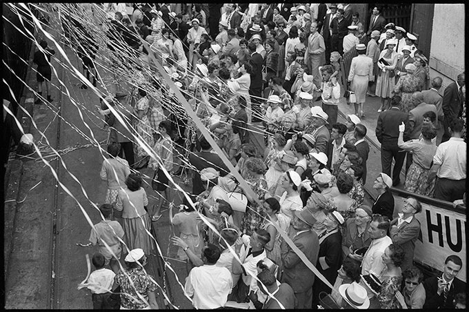 John Rykenberg,   Crowds covered in streamers on the Auckland wharves for the departure of the MV Wanganella for Sydney , 1958.