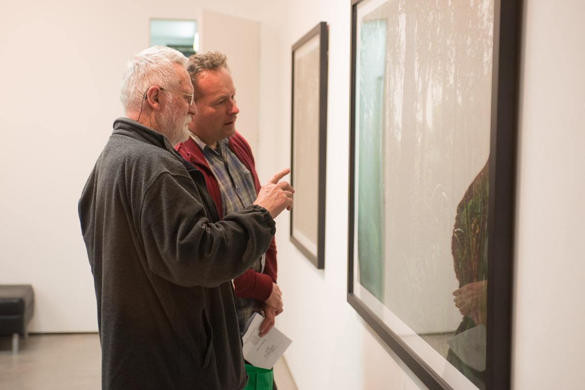 """John B. Turner discusses Ian Macdonald's work with sculptor John Radford at the opening of the exhibition """"Recent Auckland Photography"""" at Northart Gallery, 19 May, 2013."""