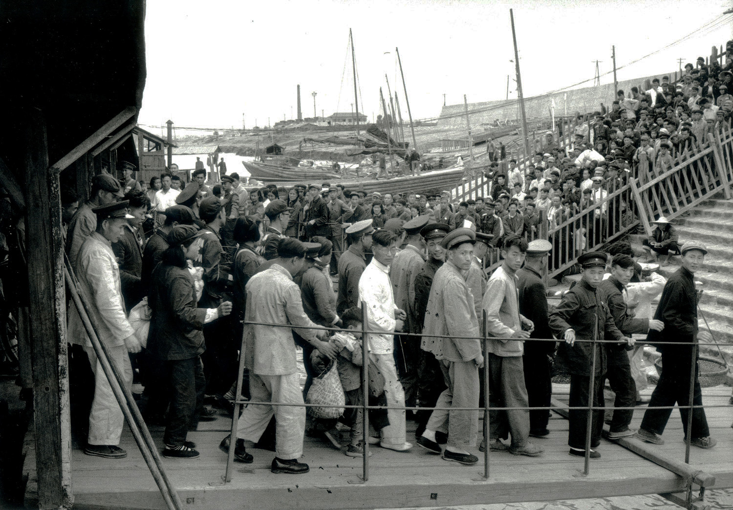A large crowd embarking and disembarking from a ferry terminal in Hunan Province, China, May 1956. (RDH C05-13a)