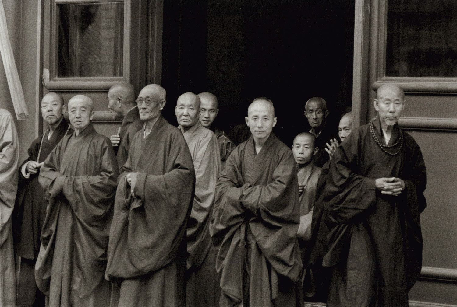 Buddhists outside the doorway of the big Temple, Peking. China, 1956. This was the year of the 2,500th anniversary of the attainment by Buddha of nirvana. (RDH C24-20)