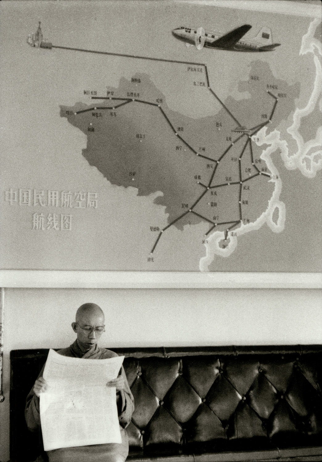 A Buddhist monk waits under a Peking-Moscow airline poster at Peking airport. China, August 1956. (RDH C147-04)