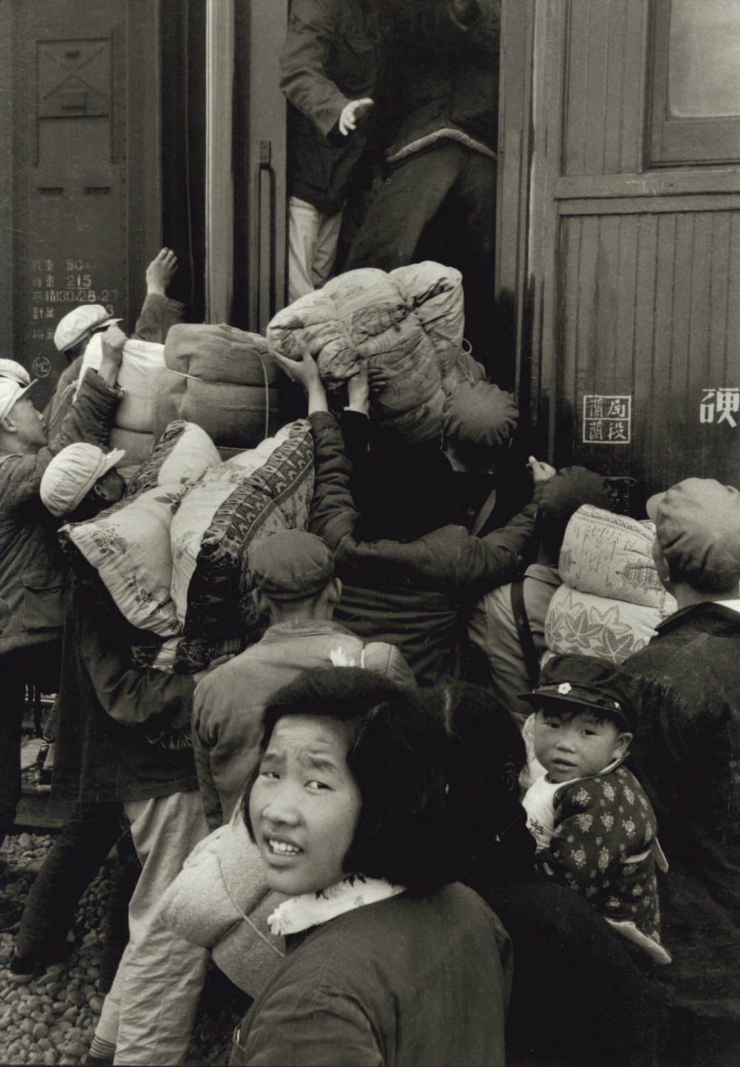 Families loading matresses and pillows onto a train at Wu Wei in Kansu. They are  