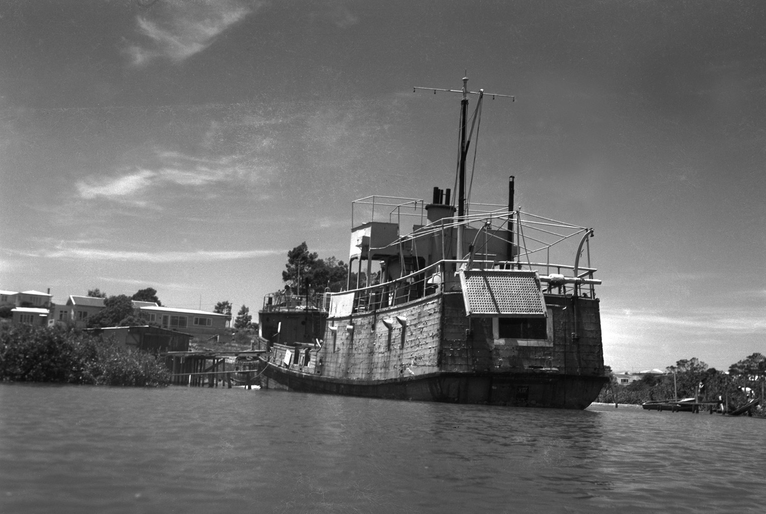 Isa lei, abandoned in the mangroves at the bottom of Wharf Road, and subsequently providing salvage materials for some, a residence for others and a playground for local kids like Gary de Forest, as related in Katy & Kula and the Kervil Kids (2011). Photographer: Jack Diamond, 1962. Auckland Libraries West Auckland Research Centre, J.T. Diamond Collection. (JTD-17M-01856-1)