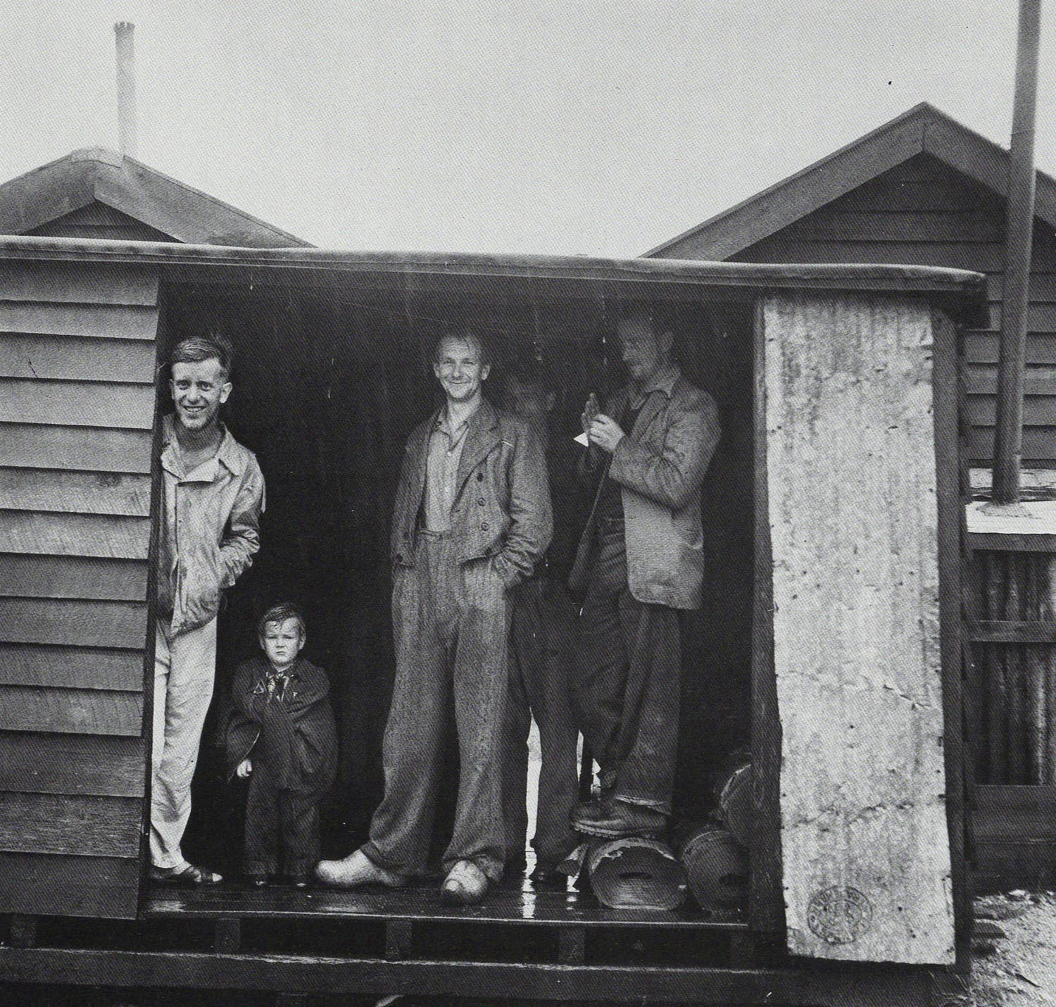 Les Cleveland.  Silver Pine Cutters Sheltering From Rain at Mussell Point, South Westland , 1955.  Witness to Change - Life in New Zealand Photographs 1940-1965 . PhotoForum/Wellington, 1985.