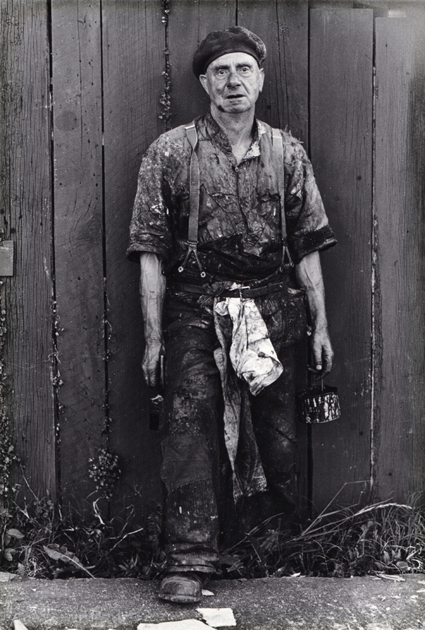 Glenn Busch.  Man painting his fence,  1973