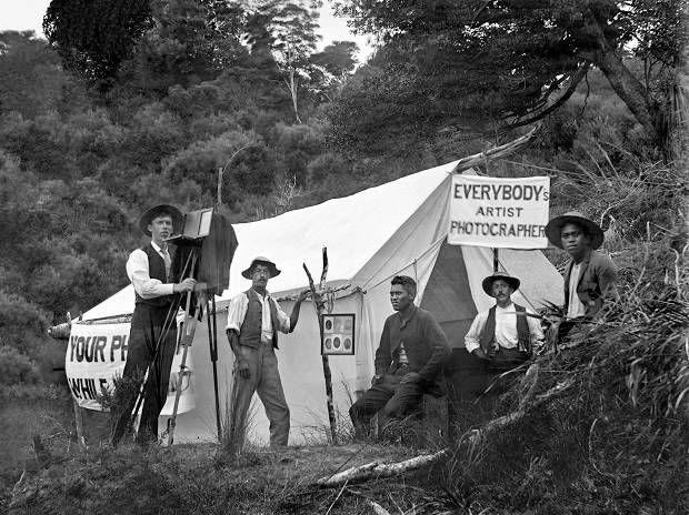 """While-you wait"" photos. Photographers Enos Pegler (l) holding camera and tripod and Charlie Dawes (second from left). Photo / Dawes collection, Auckland Libraries"