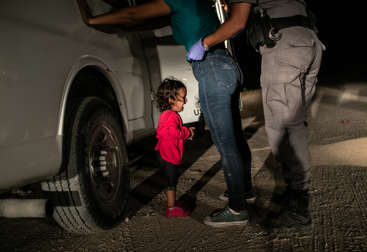 John Moore:   Yanela, from Honduras, cries as her mother Sandra Sanchez is searched by a US Border Patrol agent, in McAllen, Texas, USA, on 12 June  © John Moore