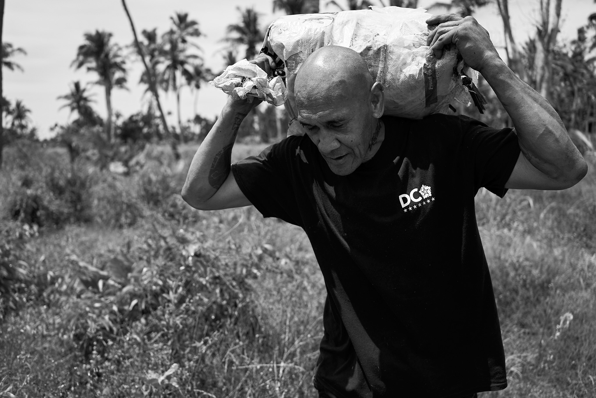 Todd Henry   Sione Ngaue carries a bag of manioke on his family's plantation near Nukunuku