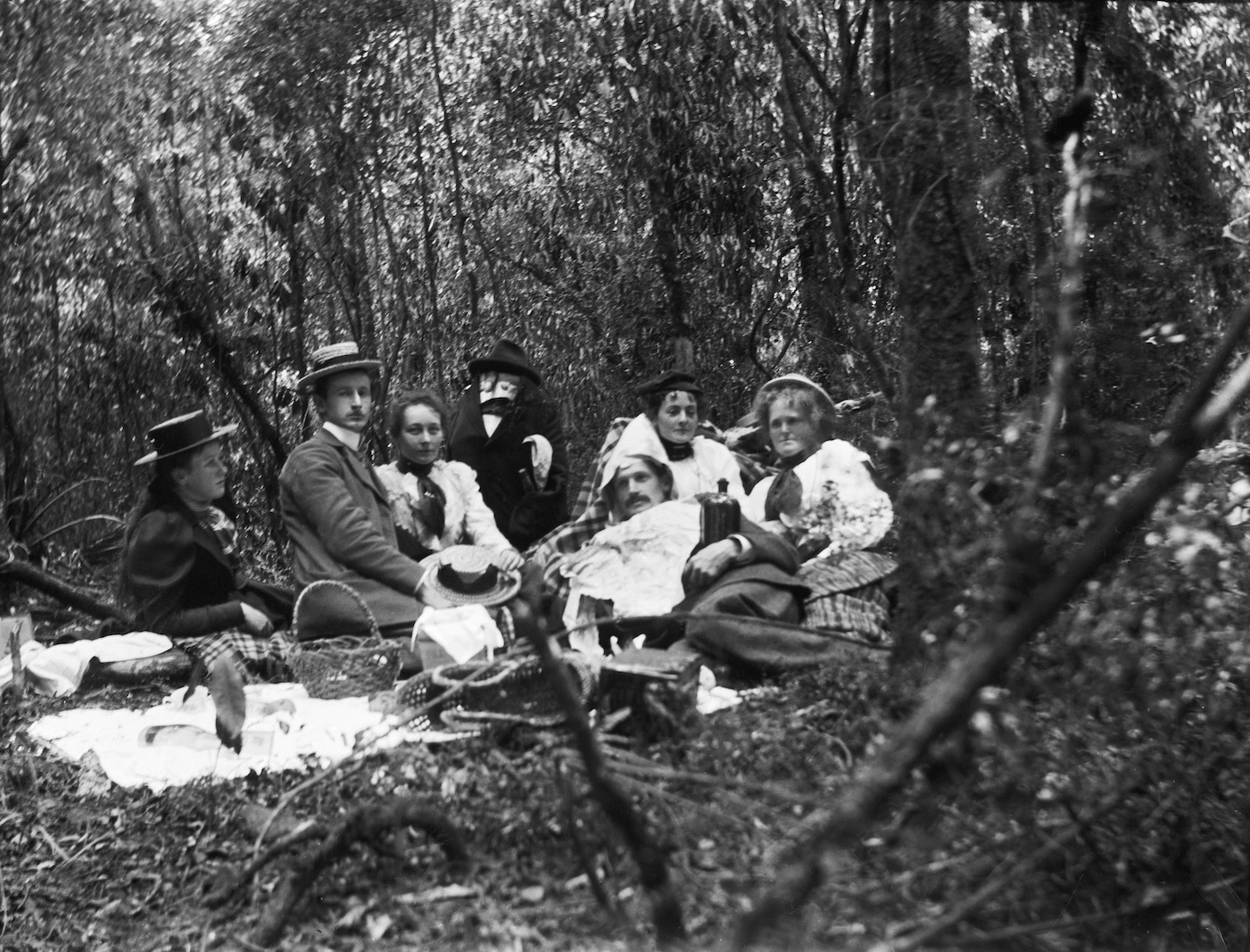 Some next level shenanigans at an Edwardian picnic in the New Zealand bush, likely North Island circa 1907-1911. Lemuel Lyes Collection.