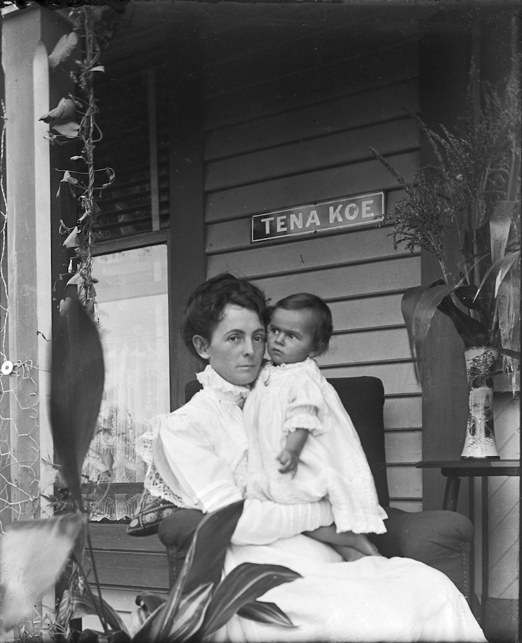 Woman and child seated below 'Tena Koe' sign at entrance to home. Likely photographed in Christchurch, New Zealand, circa 1911-1916. Lemuel Lyes Collection.