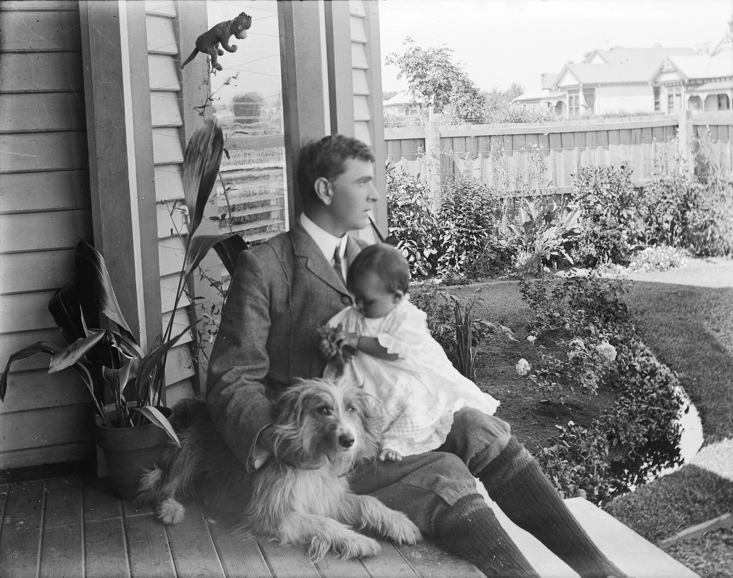 Man with baby. Possibly James and Roma Campbell. Bonus dog and toy monkey. New Zealand circa 1907-1916. Lemuel Lyes Collection.