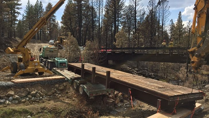 The new bridge is put into place allowing firefighters access to the ongoing wildfire. (USDA photo by Chris Bielecki)